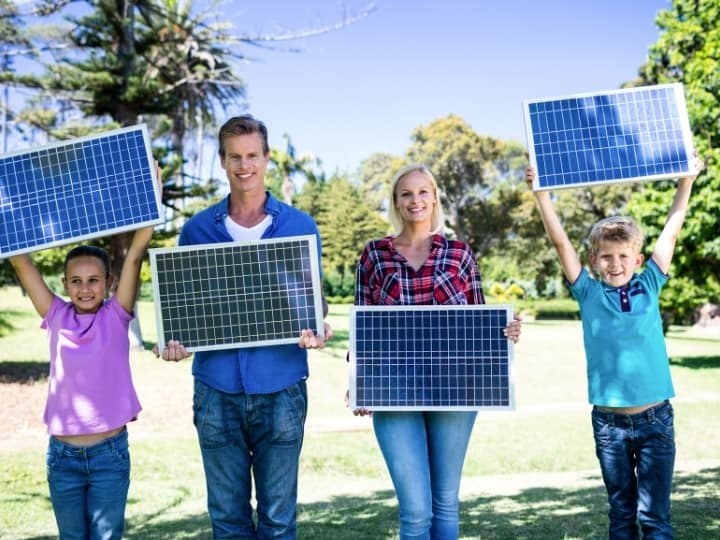 A Family Holding Up Solar Panels