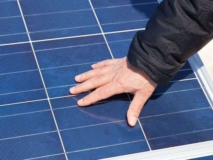 Solar Panel With a Hand on It