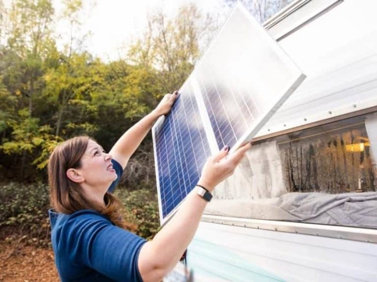 A woman passing a solar panel to an RV roof